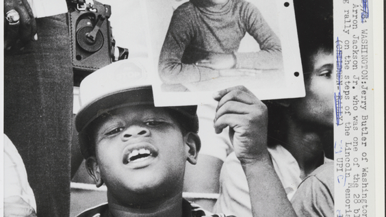Child holding photo of his cousin, victim Aaron Jackson, on steps of Lincoln Memorial in protest (5/25/81)
